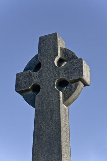 roughly-cut stone cross on cemetery in stirling