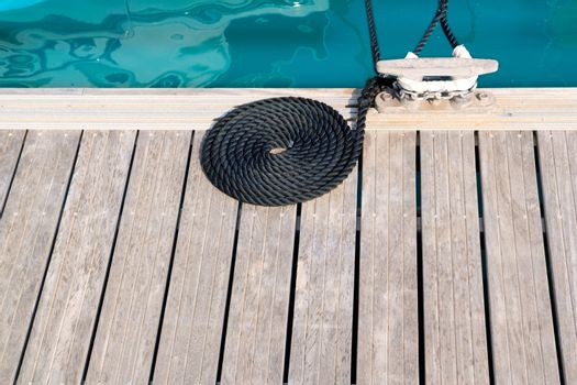 mooring wooden pier with coiled spiral rope and a bitt
