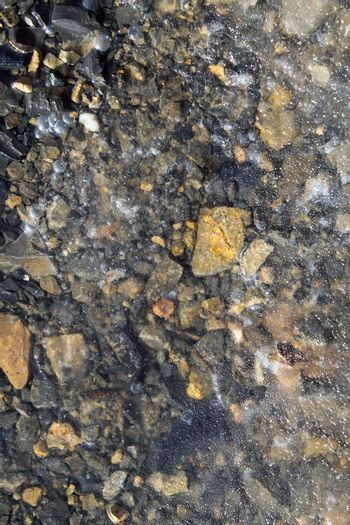 Iced stones soil in winter translucent ice