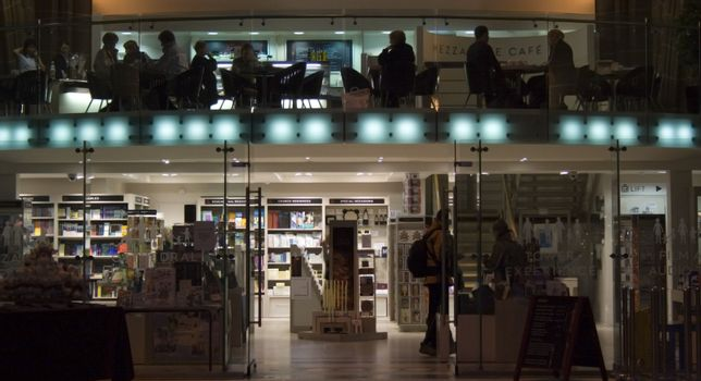 People silhouetted in a modern cafe/bookstore