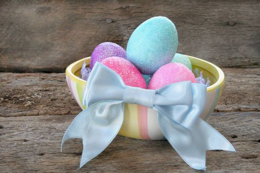 Colorful Easter eggs in a dish with a blue bow.