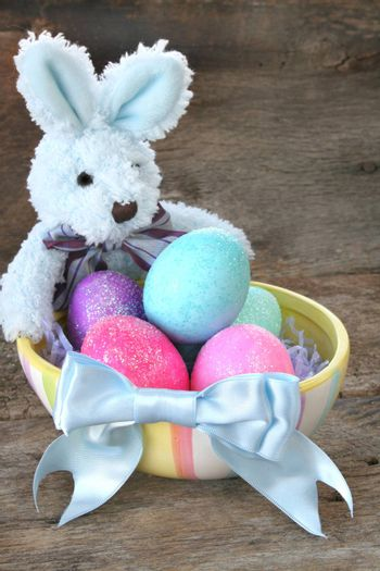 Stuffed Easter bunny with Easter eggs and a pretty blue bow.