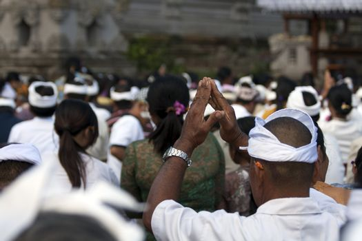 Balinese people praying at temple ceremony