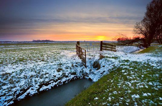 sunset over dutch farmland