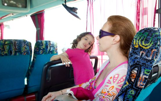 Girl and mother on tourist bus happy with sunglasses in vacations