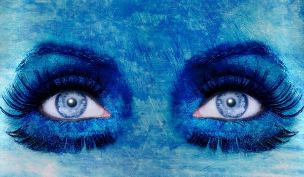 abstract blue woman eyes makeup with a grunge painted wall texture