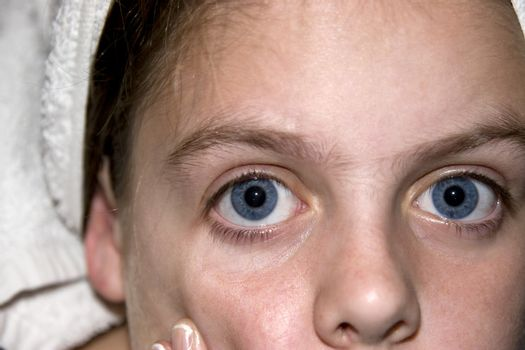 Portrait of a young teenage blue eyed girl looking straight into the camera