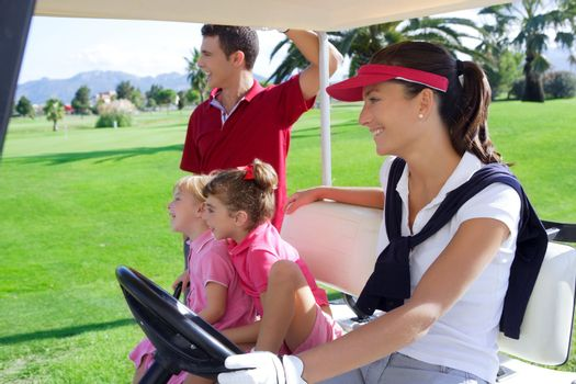 golf course family father mother and daughters on buggy in a green grass field