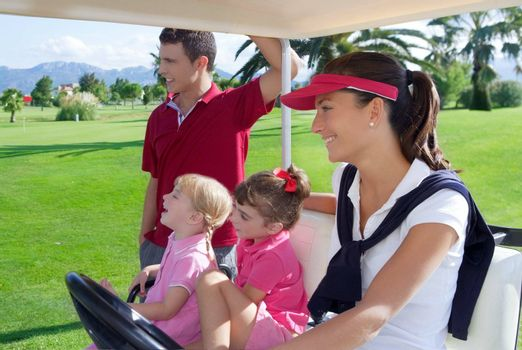 golf course family father mother and daughters in buggy green grass field
