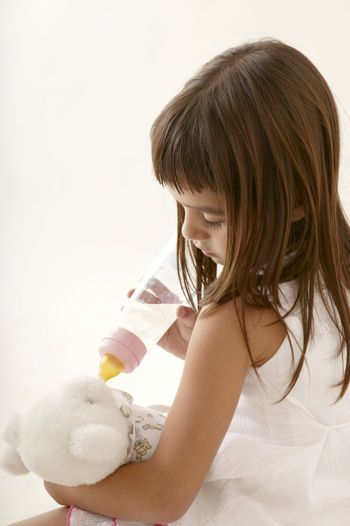 little toddler brunette girl playing with baby bottle and teddy bear