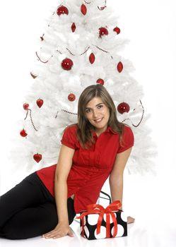 Beautiful happy woman near a white Christmas tree holding Christmas presents
