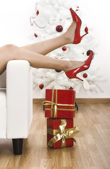 Sexy woman legs with red shoes on a Christmas environment