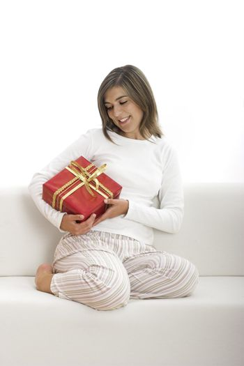 Woman in pajama seated on a sofa holding a Christmas gift