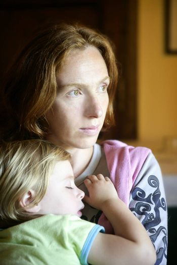 Baby toddler girl sleeping in redhead mother arms tranquil scene
