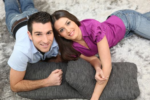 Couple laying on cushions on the floor