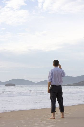 Barefoot businessman standing on a beach while talking on cell phone