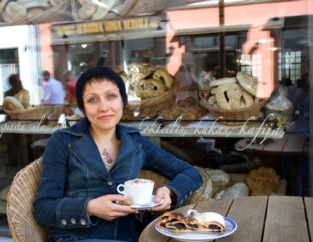 Young woman enjoying cappuccino and strudel at a cafe