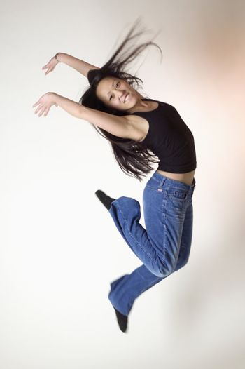 Young Asian woman jumps for joy