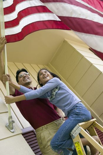 Smiling father and daughter put an American flag on their house