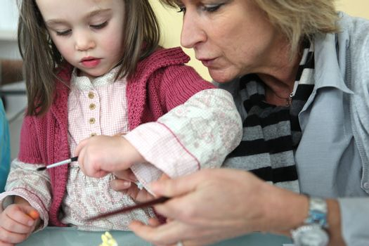 Mother repairing daughter's sleeve