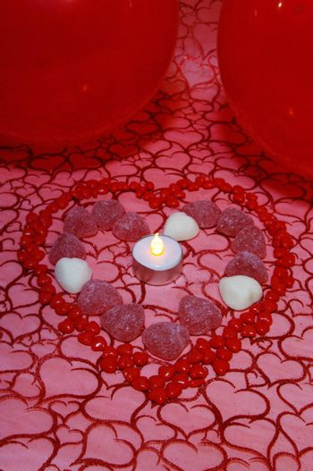 A background of material with hearts and cinnamon candies and balloons