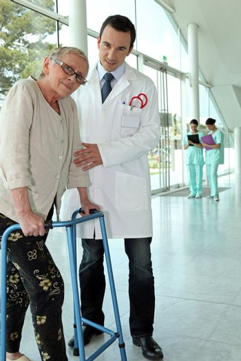 Helpful doctor and senior woman with walker