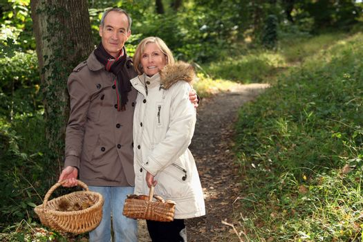 Couple with basket of chestnuts and mushrooms