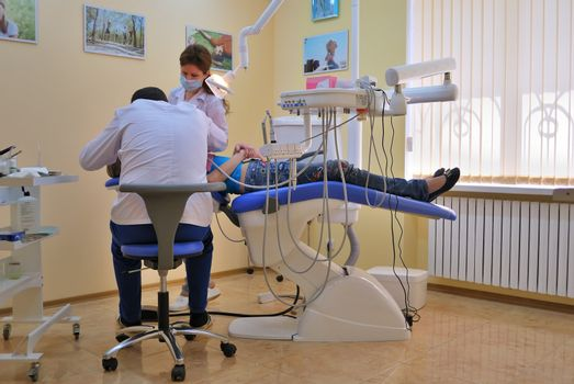 dentist and assistant operate on the patient