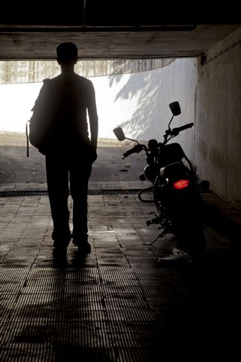 Vertical capture of a man in a white vest with ruck sack back pack stood beside a motor with its tail slights on in a tunnel