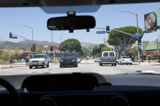 View of Hollywood Boulvard in Los Angeles, CA from a front seat inside a car.