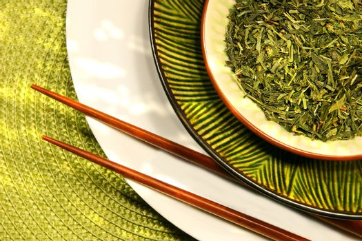 Asian chopsticks, bowls filled with herbs and green mat
