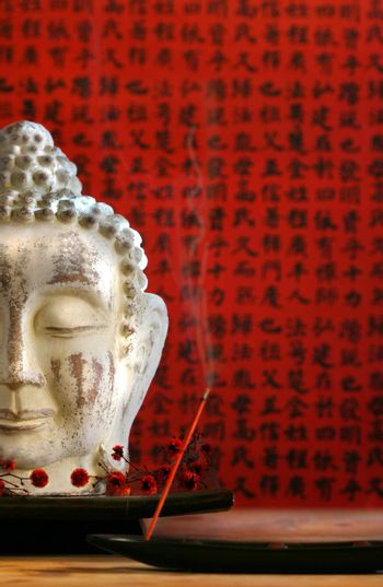 Buddha head and incense against red background