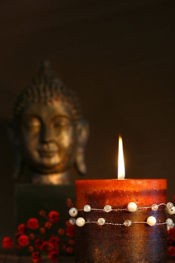 Zen candle and buddha statue with dark background