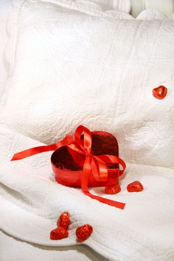 Box of chocolates with red ribbon on a bed for Valentin's day