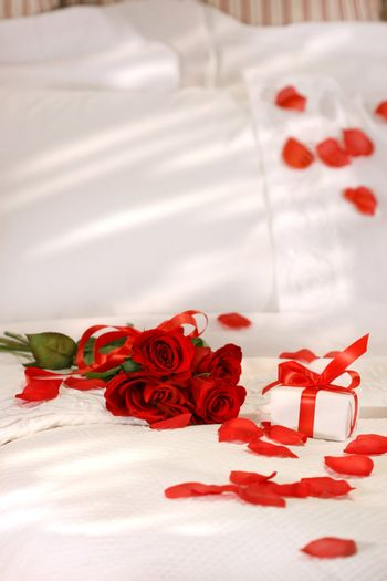 Red roses on a bed with crisp white sheets