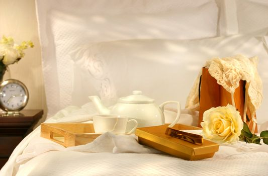 Tea in bed with chocolates and white sheets