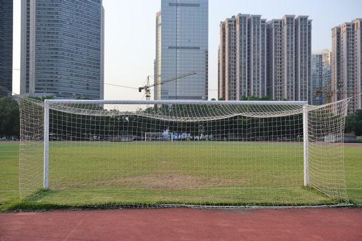 football goal with football field and buildings as background
