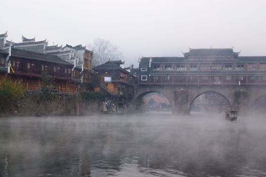 China river landscape with boat, bridge and ancient building in Fenghuang county, Hunan province, China