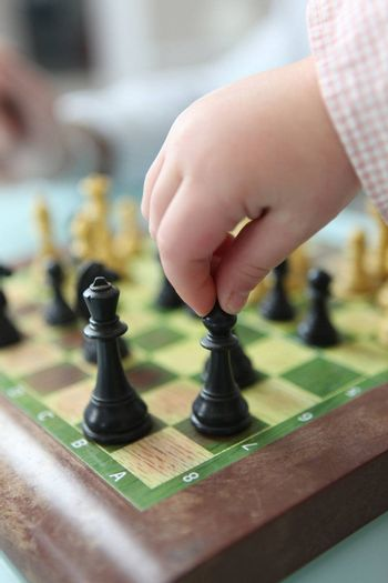 Close-up of toddler playing chess