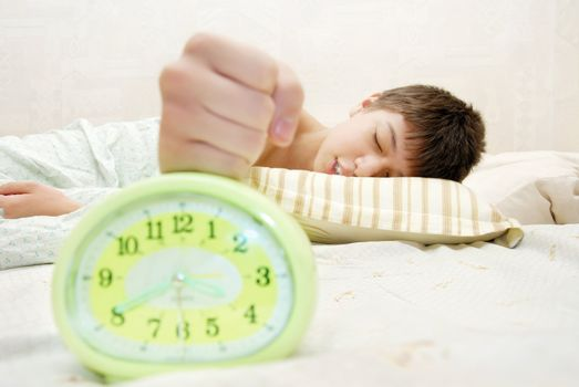 Sleeping boy hitting the alarm clock at the early morning