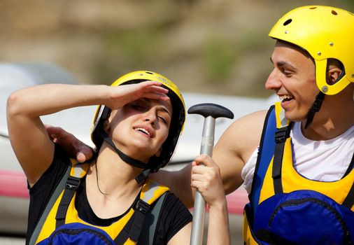 Happy couple with helmets and rafting equipment smiling