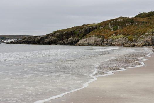 sandy coastline with hill in background. scotland, uk, europe