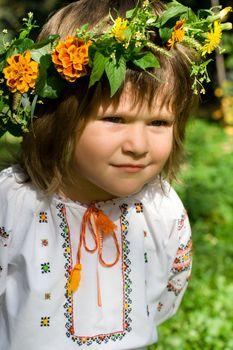 Pretty little girl dressed in Ukrainian folk costume with focused look