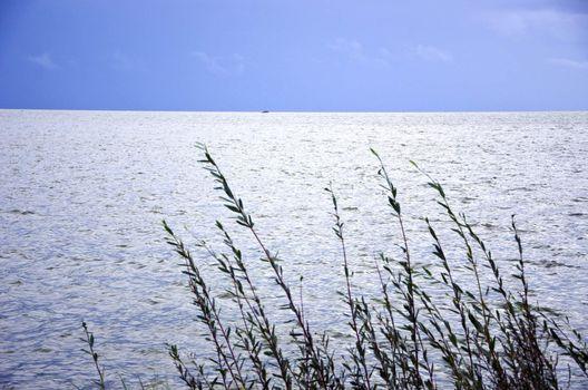 Calm sea sky landscape ship sailing in distance.