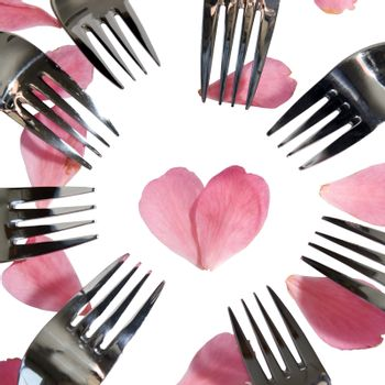 forks surrounding a heart shape petal with rose petals for a concept on romantic dining on white background