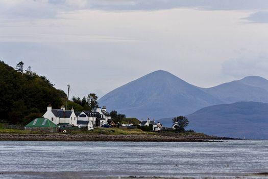 small housing estate at the sea in north scotland with mountains in background