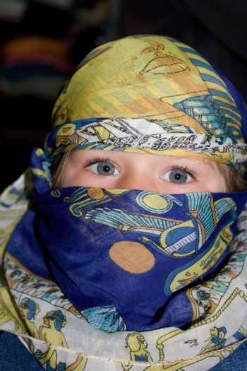 Curious European child dressed in headscarf in the Arabian manner