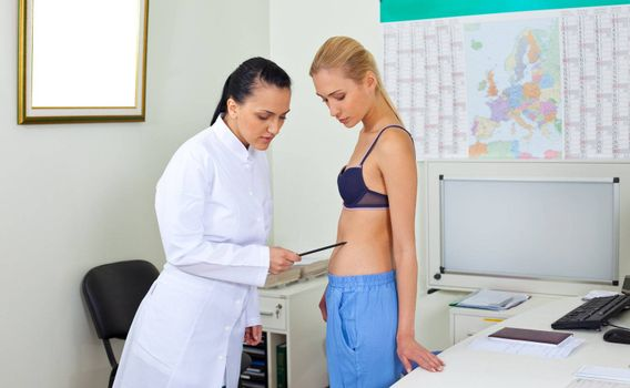 Female doctor in white uniform examining blonde woman's body