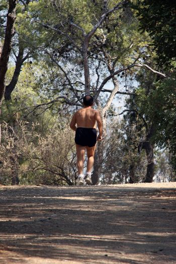 man is jogging in forest half nude