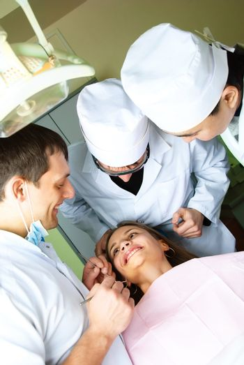 three dentists bend over the patient and examine her teeth